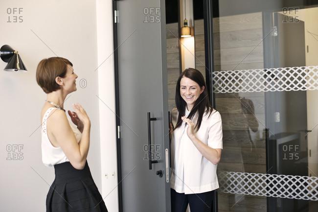 Businesswomen laughing by door