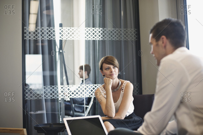 Businesswoman listening attentively to male colleague