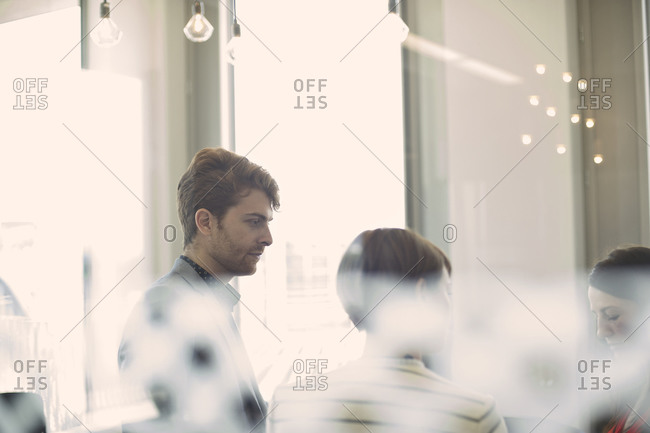 Colleagues meeting seen through glass partition