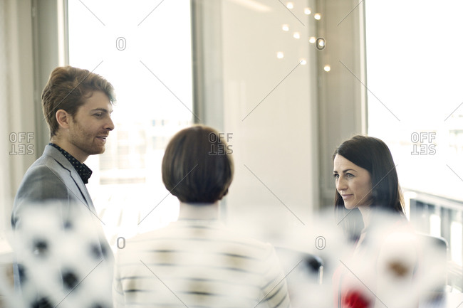 Co-workers meeting seen through glass partition