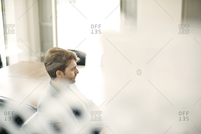 Businessman at meeting seen through glass partition
