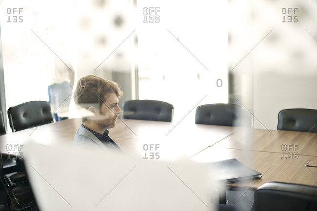 Meeting attendee seen through glass partition