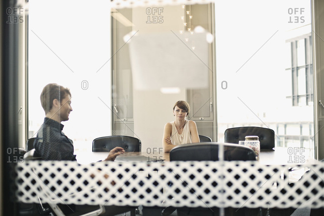 Colleagues at meeting seen through glass partition
