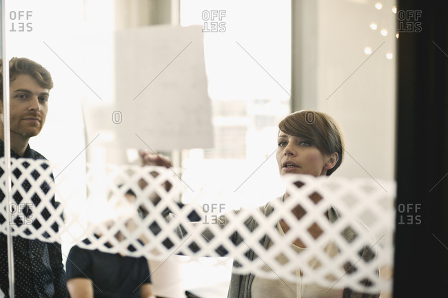 Businesswoman explaining something at meeting behind glass wall