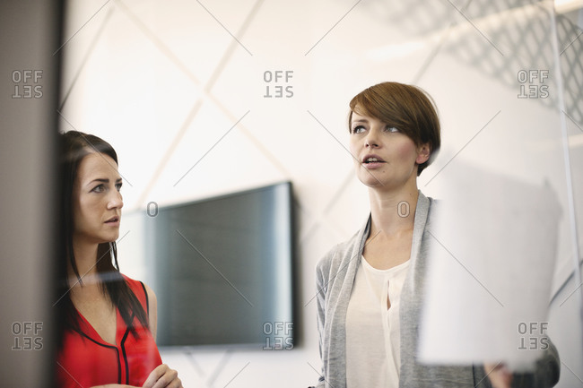 Businesswoman explaining things at meeting behind glass wall