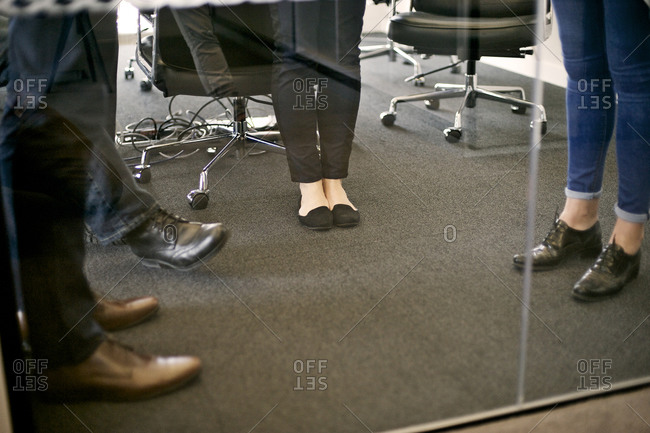 Feet of coworkers at meeting behind glass partition
