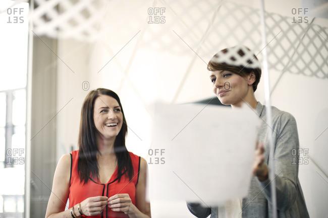 Businesswomen at meeting behind glass wall