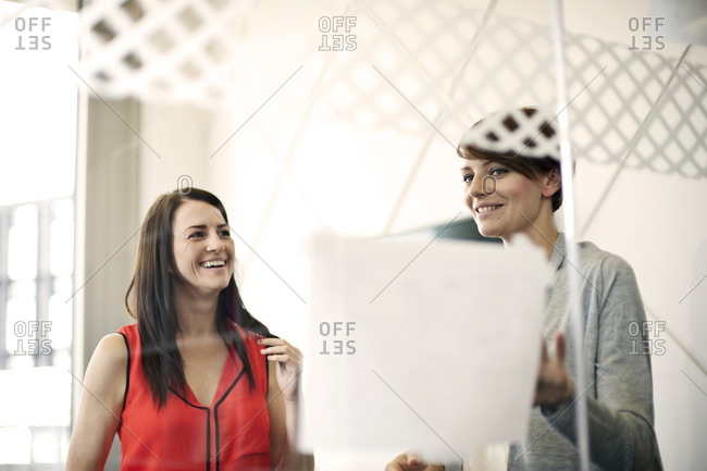 Two businesswomen at meeting seen through glass wall