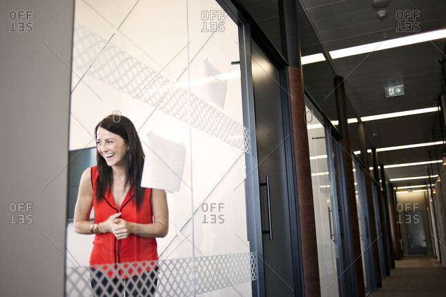 Businesswoman laughing behind glass wall