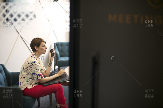 Businesswoman with portfolio and smartphone at job interview