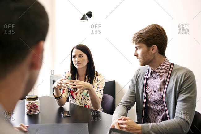 Coworkers listen to colleague at meeting
