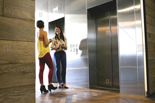 Businesswomen talking near elevators
