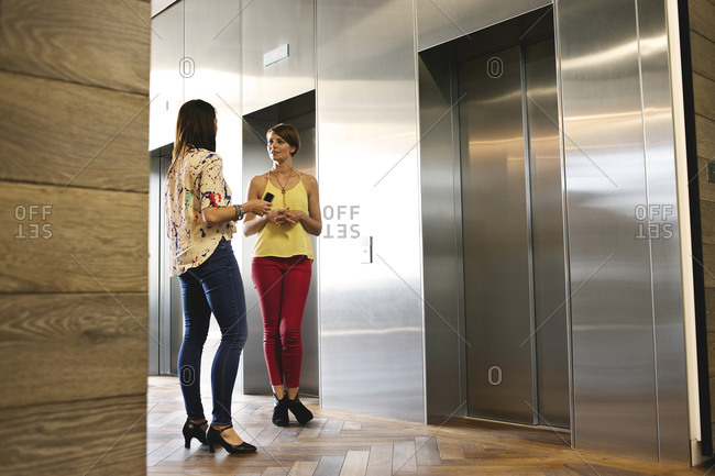 Businesswomen talking near elevator doors