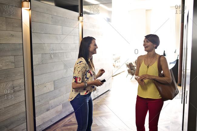 Businesswomen talking near elevator bay