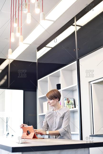 Businesswoman using tablet computer in break room