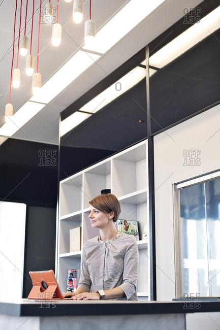 Thoughtful businesswoman using tablet computer in break room
