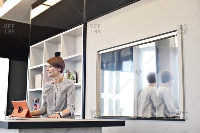 Smiling businesswoman using tablet computer in break room
