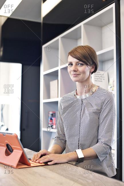 Proud businesswoman using tablet computer in break room