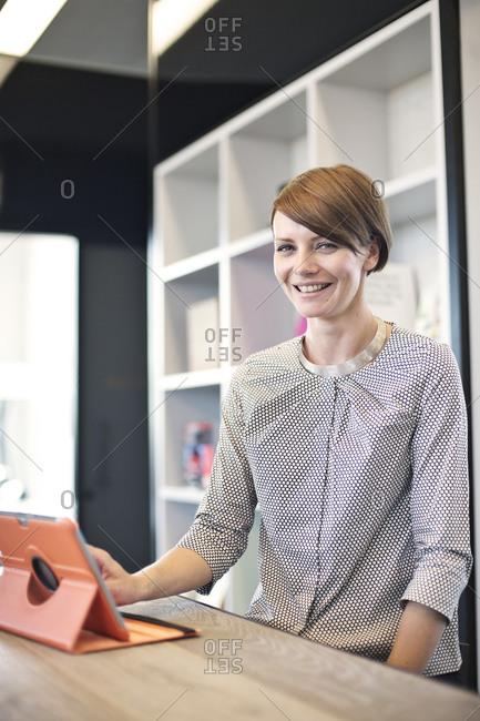 Happy businesswoman using tablet computer in break room