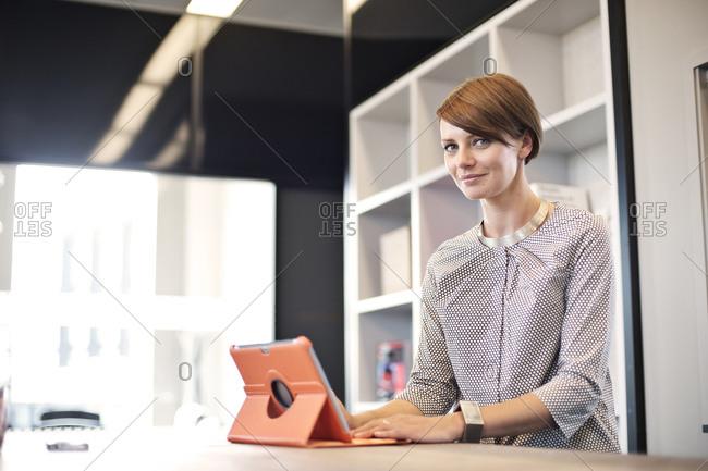 Confident businesswoman using tablet computer in break room