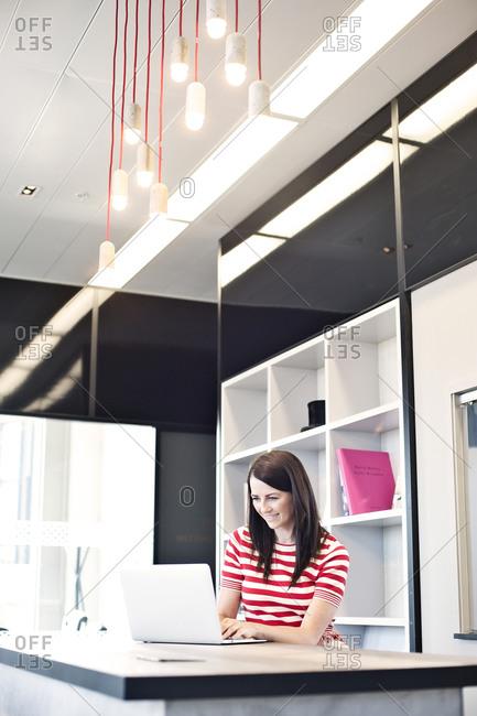 Businesswoman in break room using laptop computer