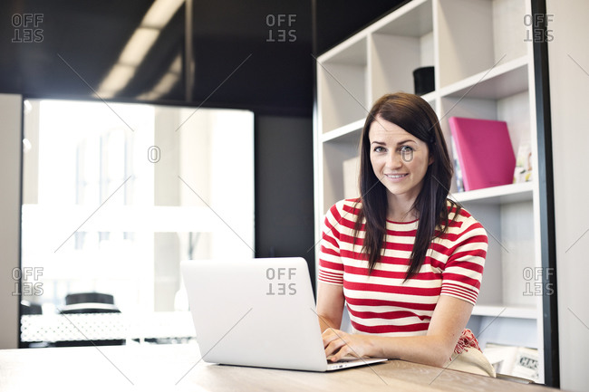 Smiling businesswoman in break room using laptop computer