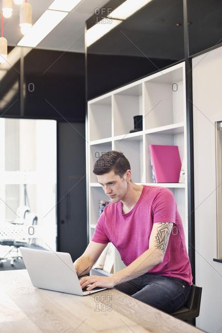 Tattooed businessman using laptop computer