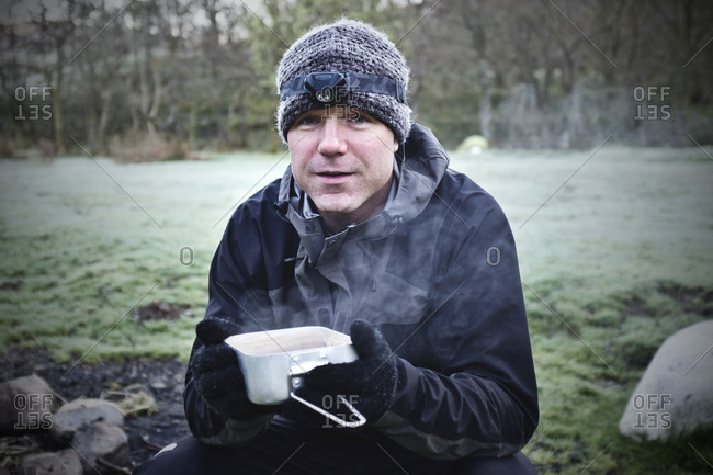 Man about to drink hot soup from a tin pot