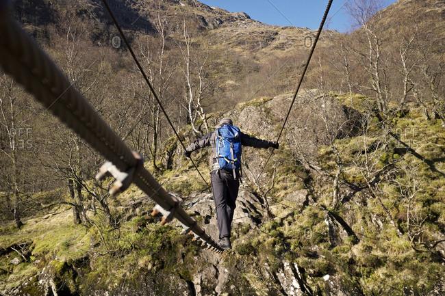 Hiker crossing rope bridge