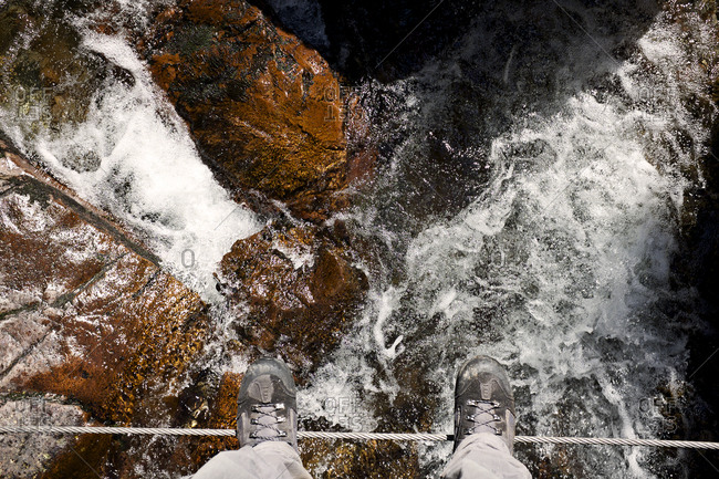 Hiker's feet on rope bridge over swift-running stream