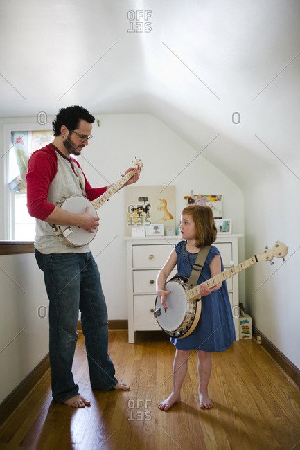 Father and daughter playing banjo together