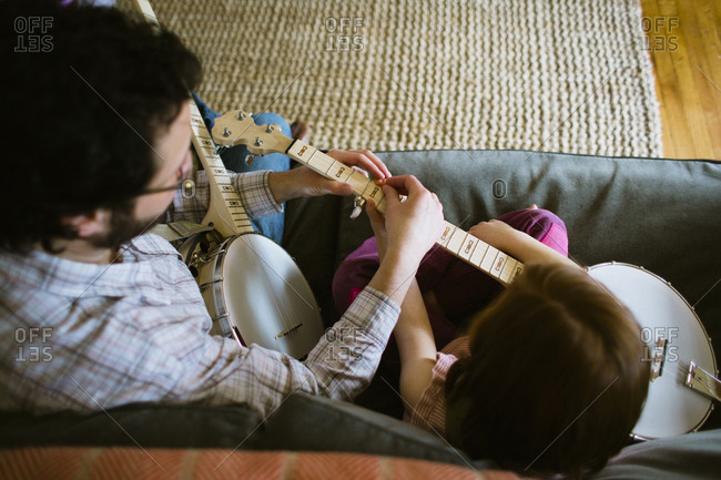 Overhead view of father and daughter practicing on banjo