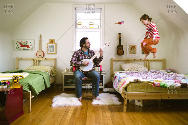 Redhead girl jumping on bed while her father playing banjo