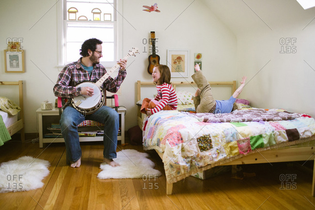 Children playing on bed while their father playing banjo