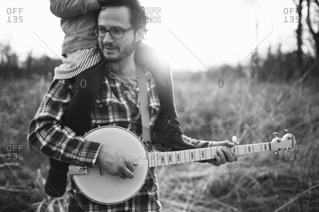 Close up of father carrying child on shoulders and playing banjo
