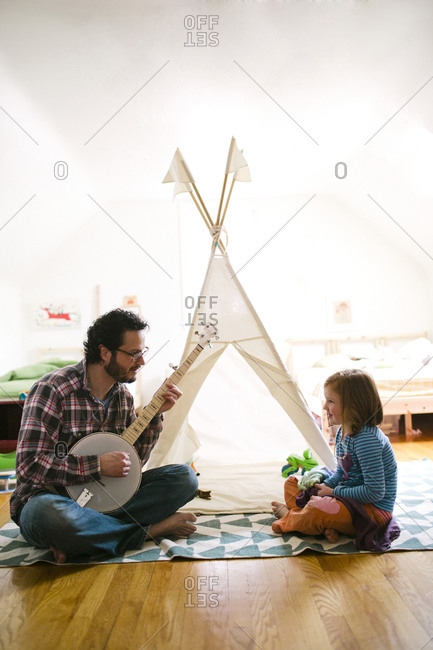 Father playing banjo to his daughter