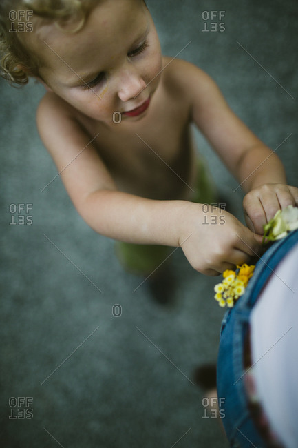 Overhead view of boy placing yellow wildflowers in an adult's back pocket