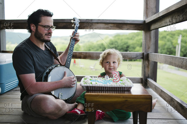 Father playing banjo to his three years old son