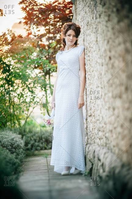 Bride leaning on a wall of the chapel
