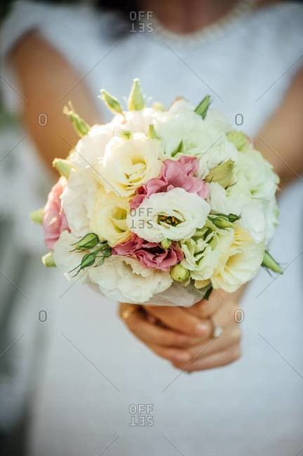 Mid section view of a bride holding bridal bouquet