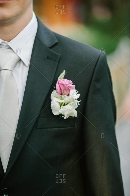 Man standing in a wedding suit with a boutonniere