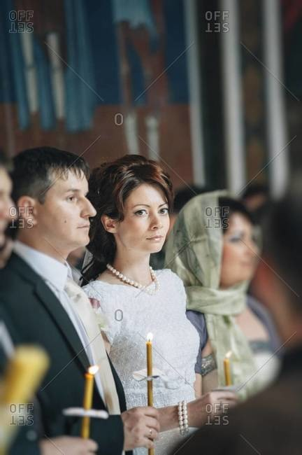 Bride and groom standing with candles at an Orthodox wedding ceremony