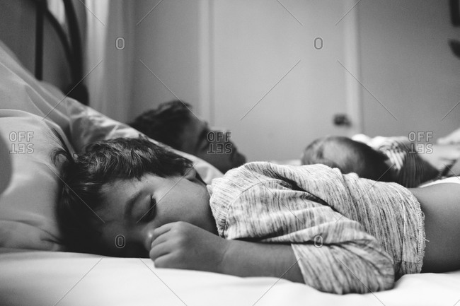 Boy sleeping with his family in bed