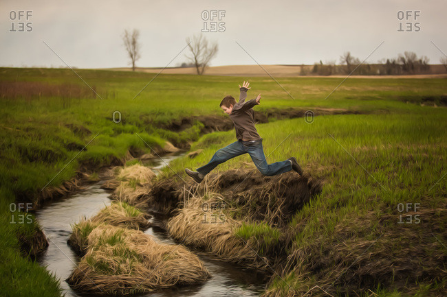 Boy jumping over a brook