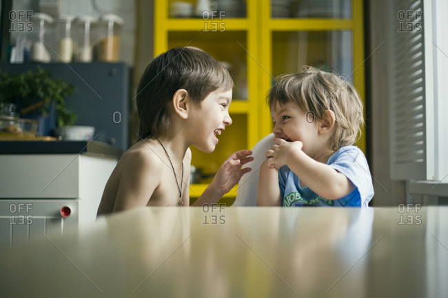 Brothers laughing in kitchen