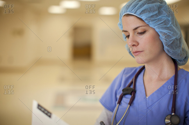 Nurse reading medical chart in hospital