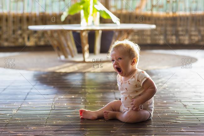 Baby yawning on floor