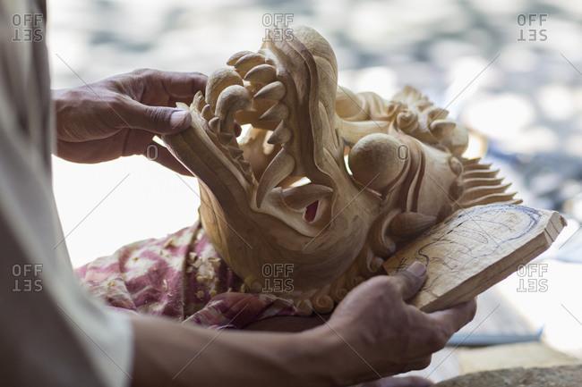 Wood worker examining piece in studio