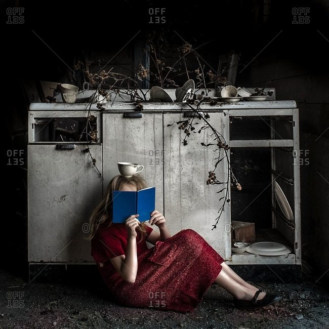 Girl reading with a cup on her head
