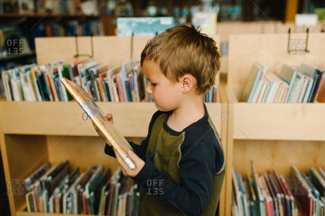 A young boy selecting a book from the library
